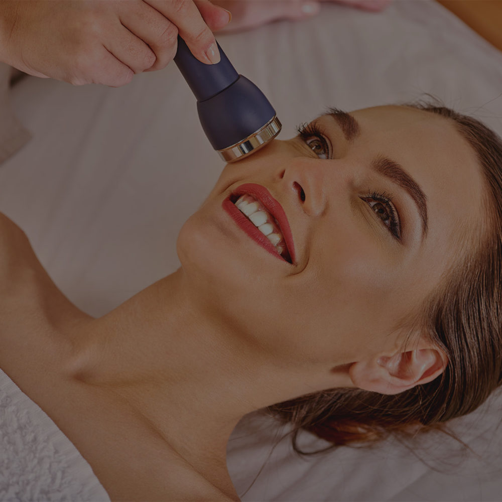 Young woman receiving electric facial massage.